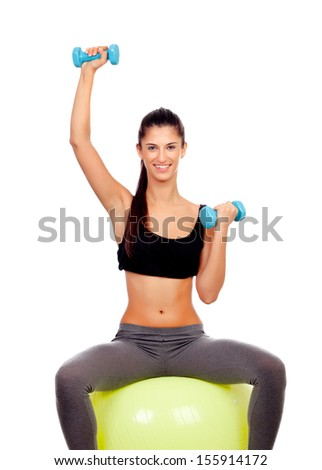 Attractive girl lifting weights sitting on a ball isolated on white background