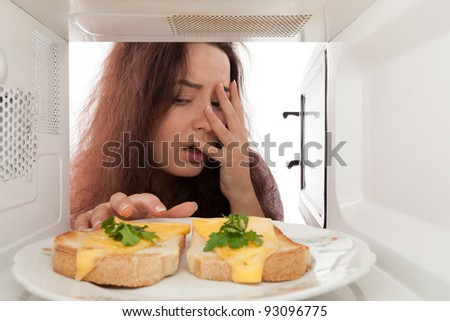 Attractive girl looks in a microwave - stock photo