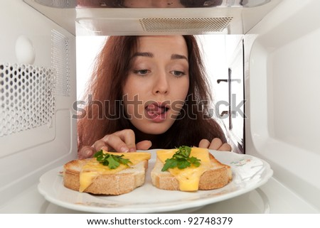 Attractive girl looks on toasts in a microwave and lick - stock photo