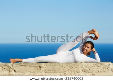 Attractive girl meditating and exercising in yoga pose on high altitude with amazing view on background, healthy woman smiling during yoga training outdoors, woman practicing yoga enjoying sunny day - stock photo