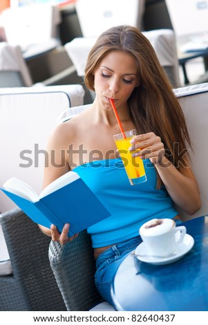 attractive girl reading book in coffee shop - stock photo