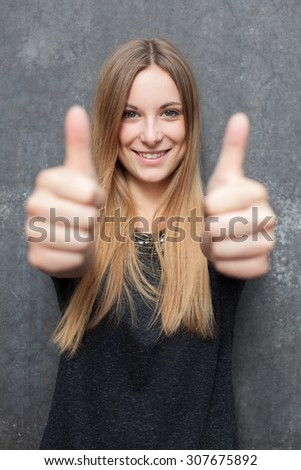 Attractive girl showing thumbs up with both hands - stock photo