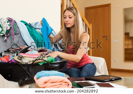 Attractive girl sitting on sofa and packing luggage - stock photo