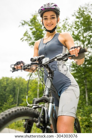 Attractive girl standing with her bicycle on the forest road, looking at camera and smiling.