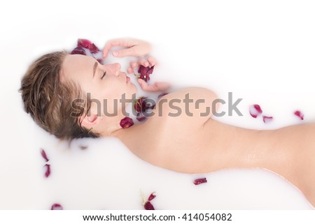 Attractive girl takes a bath with milk and rose petals. Spa treatments for skin rejuvenation - stock photo