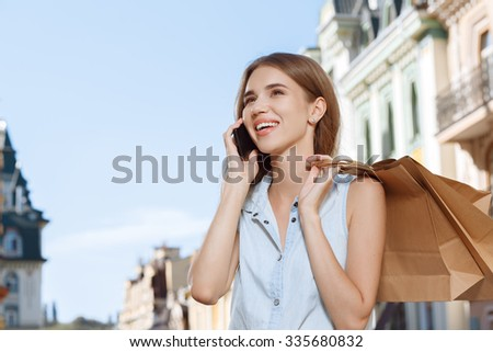 Attractive girl talking on the phone while walking in the city with shopping bags - stock photo