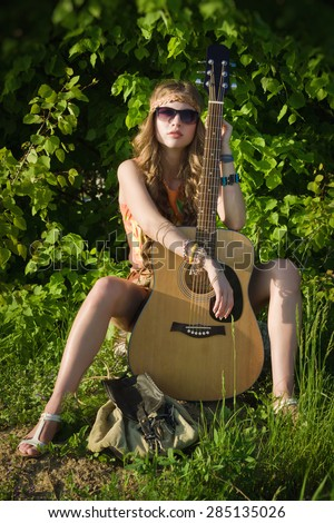 Attractive girl traveling with her guitar - stock photo