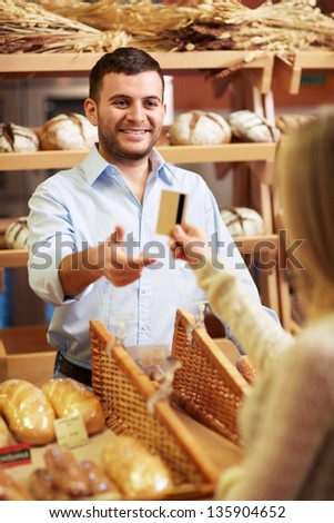 Attractive girl with a credit card at the counter - stock photo