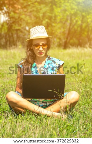 attractive girl with a laptop in the grass - stock photo