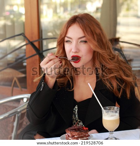 Attractive girl with beautiful hair sitting in a cafe eating cake and smiling outdoors