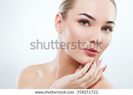 Attractive girl with big green eyes, dark eyebrows, brown hair and naked shoulders holding hands with pink manicure near face, light nude make-up, white studio background, beauty photo - stock photo