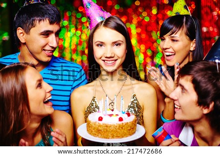 Attractive girl with birthday cake and her friends having party - stock photo