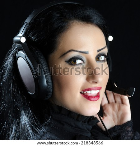 Attractive girl with headset against a black background - stock photo