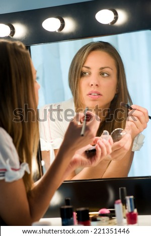 Attractive girl with long brunette hair applying her makeup in a mirror admiring her reflection in a beauty concept, view from behind of the reflection