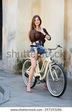 Attractive girl with long fair hair, wearing on short blouse and shorts, is posing on bicycle on the street of old European city, full body - stock photo
