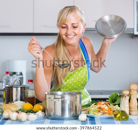 Attractive girl with long hair cooking vegetables in kitchen - stock photo