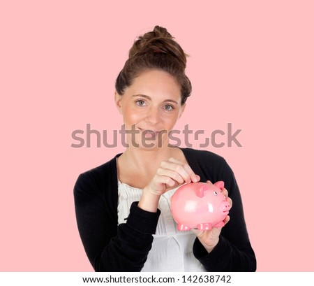 Attractive girl with money box on a pink background