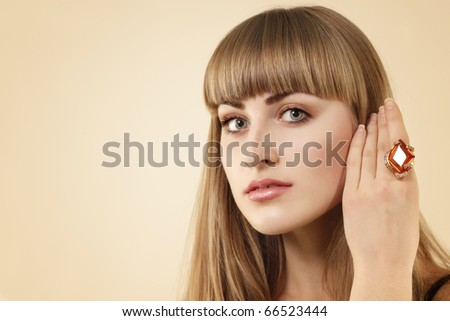 attractive girl with natural make-up and jewelry over beige background - stock photo