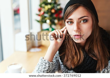 Attractive girl with nude make up and brown hair wearing gray sweater and black scarf and black hat sitting in cafe near big window, copy space. - stock photo
