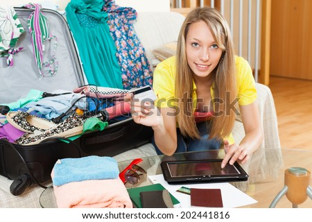 Attractive girl with packed suitcase booking hotel for vacation online with credit card  - stock photo