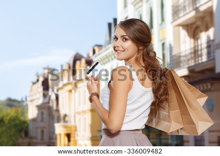 Attractive girl with shopping bags and credit card in the city - stock photo
