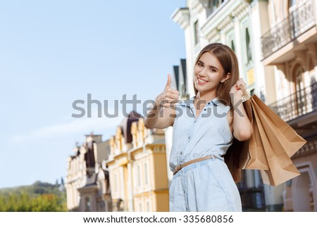 Attractive girl with shopping bags showing thumbs up