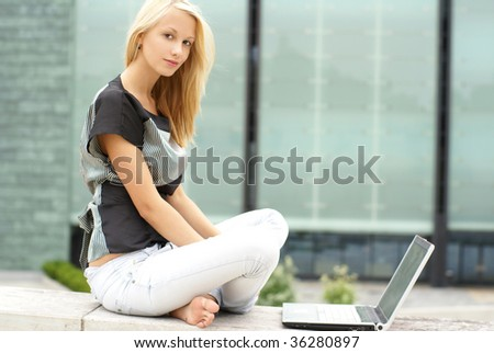 Attractive girl with the notebook over modern architecture background