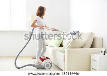 Attractive girl with vacuum cleaner on light background - stock photo