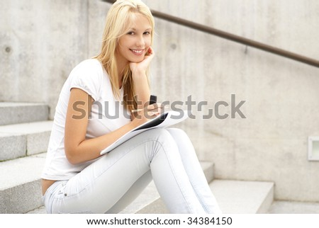 Attractive girl writes something in a diary
