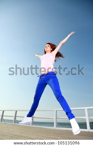 Attractive girl Young woman jumping in the sky - stock photo