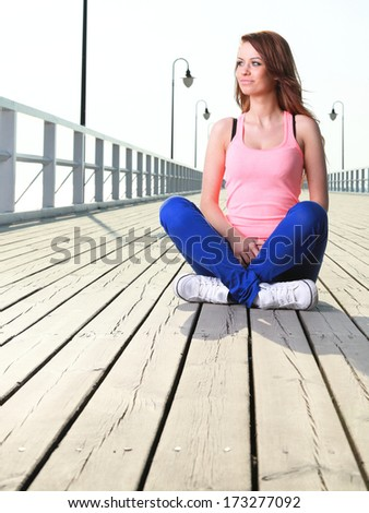 Attractive girl Young woman on pier Sits Crossed Legged Relaxing Old Wooden Pier outdoor - stock photo