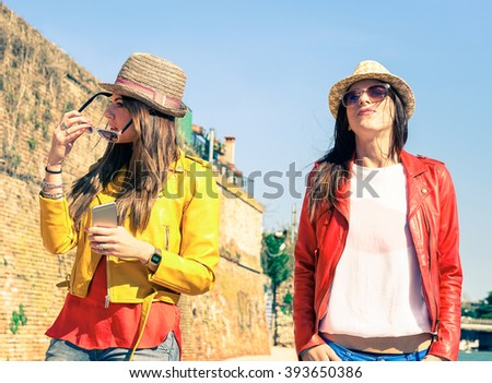 Attractive girlfriends in arrogant posing after couple discussion - Young women with serious face expression standing outdoor - Concept of human moods and modern relations - Main focus on left girl - stock photo
