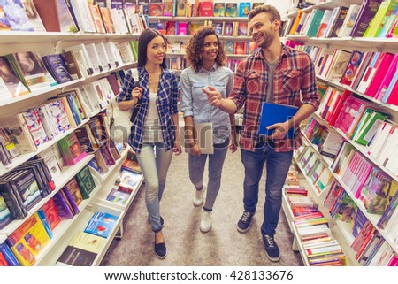 Attractive girls and guy are talking and smiling while choosing book at the bookshop - stock photo