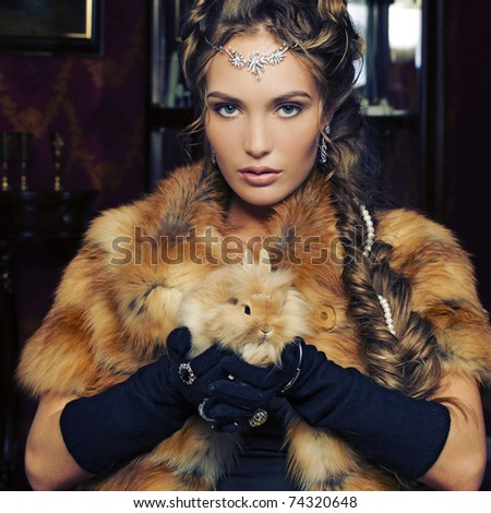 Attractive glamorous woman in fox fur coat with rabbit in her hand.