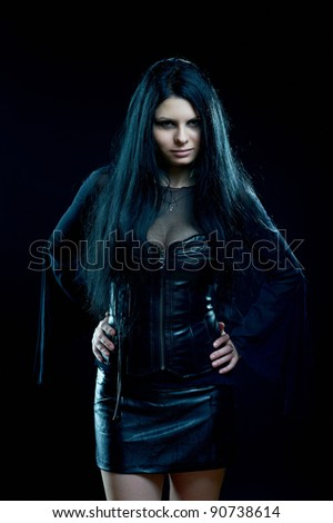 Attractive goth girl standing on black