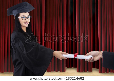 Attractive graduate in graduation gown given certificate on stage  - stock photo
