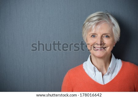 Attractive grey-haired senior woman with a beaming smile posing against a dark grey background with copyspace and vignetting - stock photo