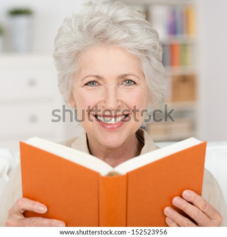 Attractive grey haired senior woman with a lovely smile relaxing at home reading a book - stock photo