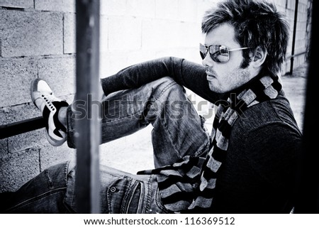 attractive guy sitting with his sunglasses and scarf - stock photo
