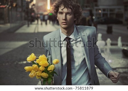 Attractive guy with bunch of tulips - stock photo