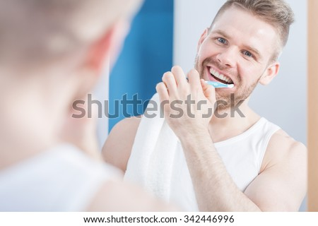 Attractive guy with perfect smile brushing his teeth - stock photo
