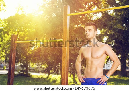 Attractive guy working out outdoors on a sunny summer day - stock photo