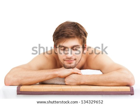 attractive handsome man resting in a spa massage center, lying on table relaxing closed eyes isolated over white background with copy space, concept of men beauty health care - stock photo