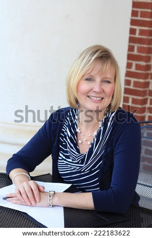 Attractive Happy and Smiling Business Professional Business Woman Sitting Wearing a Blue Shirt