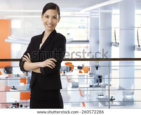 Attractive, happy, asian businesswoman at high-tech business office with arms crossed. Smiling, arms crossed, standing upstairs. Copyspace. - stock photo