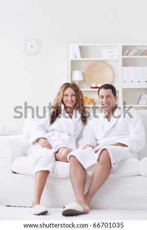 Attractive happy couple in robes at home - stock photo