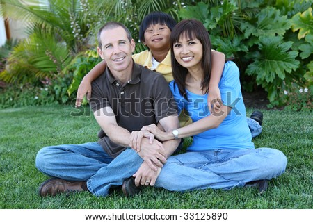 Attractive happy family outside their home having fun - stock photo