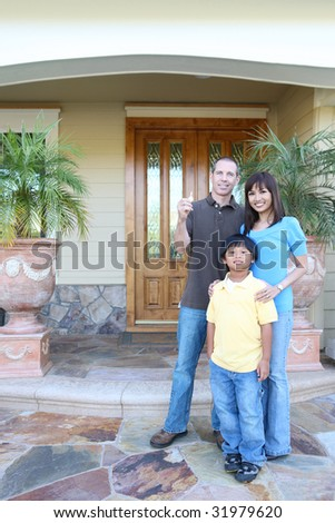 Attractive happy family outside their home with key - stock photo