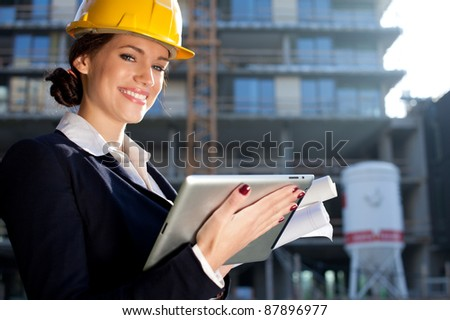 Attractive happy female construction engineer/architect with a tablet computer at a construction site - stock photo