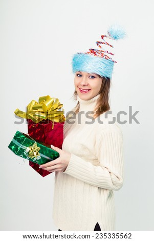 Attractive happy girl in an unusual Christmas hat with gift boxes - stock photo